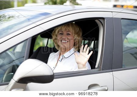 Beautiful old happy elderly driver woman 55-60 years in jacket Driving a Car
