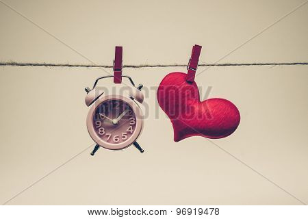A clock and a red heart hung together on a rope / time and love concept