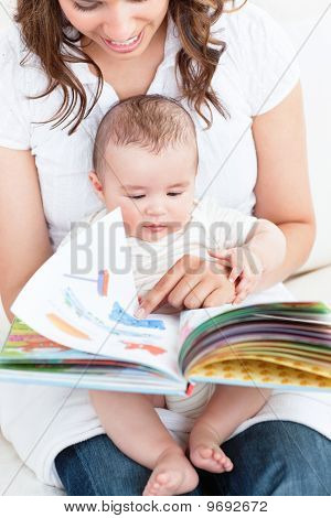 Happy Mother Showing A Book To Her Baby Sitting In The Sofa At Home