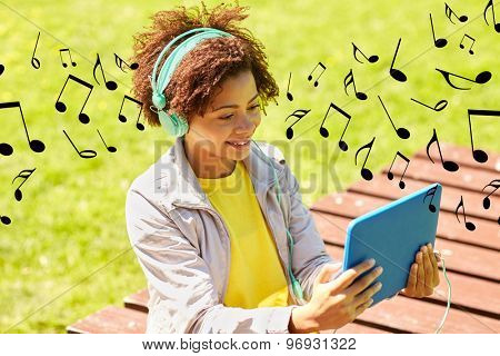 people, summer, technology and leisure concept - happy african american young woman in headphones with tablet pc computer listening to music or watching video outdoors over notes background