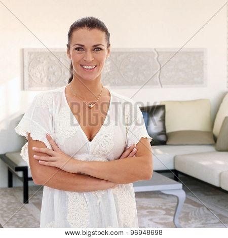 Confident woman smiling at home, arms crossed, looking at camera.