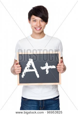 Young man hold with chalkboard showing A plus mark