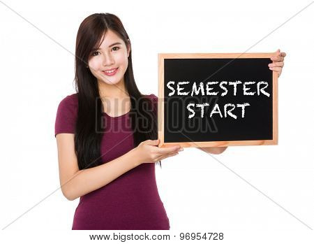 Asian woman hold with the blank chalkboard showing semester start on board