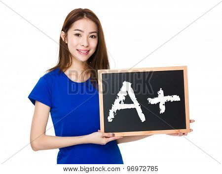 Student hold with wooden chalkboard showing mark A plus