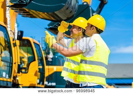 Asian worker at construction machinery of construction site or mining company poster