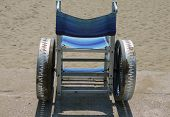 Special wheelchair to move around on the sand of the beach poster