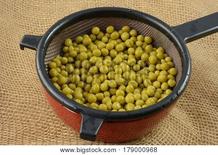 Canned sweet peas draining in strainer in bowl to lower salt content