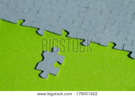 One jigsaw puzzle piece cut out on green background with copy space
