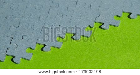 jigsaw puzzle pieces on green background with copy space