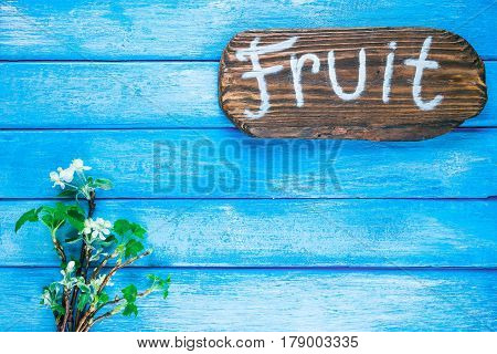 Background of narrow wood planks painted in blue. Bunch of blooming apple tree and young black current twigs. Wood signboard with text 'Fruit' as title bar