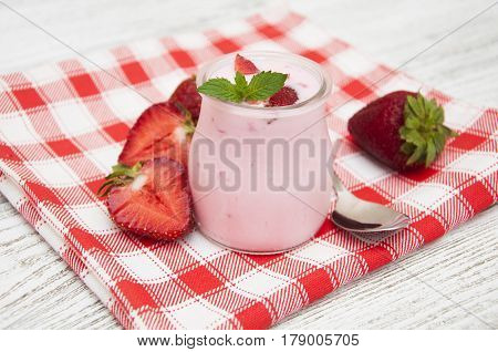 Strawberry homemade yogurt with fresh strawberries on a wooden background