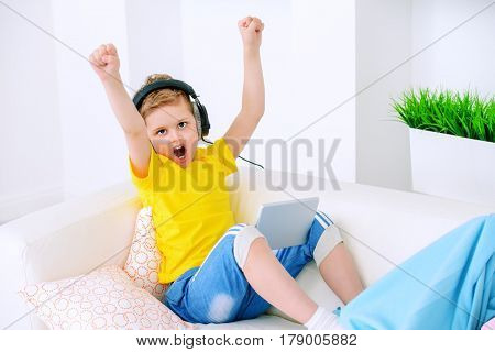 Joyful excited boy listening to music in headphones at home. Happy childhood. Activity for children.