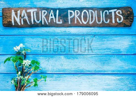 Background of narrow wood planks painted in blue. Bunch of blooming apple tree and young black current twigs. Wood signboard with text 'Natural products' as title bar