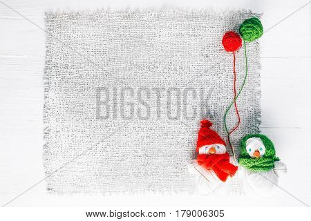 Knit shop background with couple of handmade snowmen of yarn skeins holding wool balls. White wood and burlap background