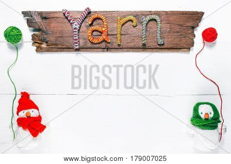 Knit shop background with title wood sign 'Yarn' of handmade letters and couple of handmade snowmen of yarn skeins holding wool balls. White wood background