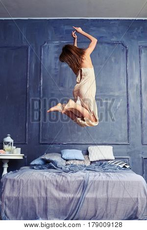 Back view of a female in the air. Woman jumping with knees bent. Wearing long nightgown having fun early in the morning