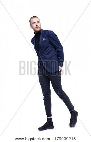 Fashion shot of a stylish bearded man wearing jeans and classic jacket. Full length portrait. Isolated over white.