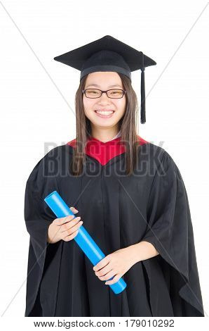 Happy university student in graduation gown and cap. Portrait of east Asian female model standing on plain background.