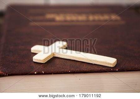 a christian cross and bivle on wooden background