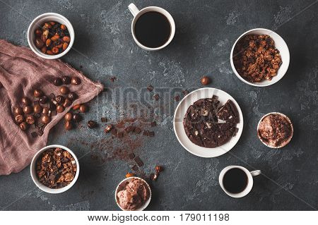 Chocolate cake cups of coffee chocolate muesli and chocolate ice cream on dark background. Flat lay top view
