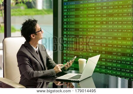 Smart businessman look at head-up display stock market board. He uses it for decision to order stock on his smartphone. Head-up Display Concept