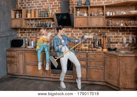 Daughter Singing And Mother Pretending Playing On Wisp In Kitchen