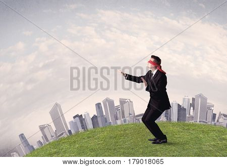 Young blindfolded businessman steps on a a patch of grass with a grey buildings in the background