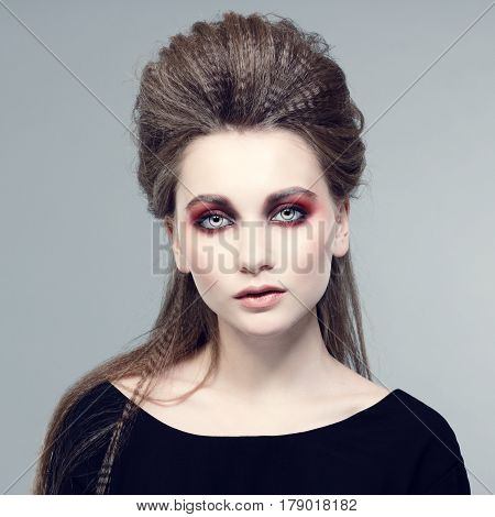 Fashionable photo. Beautiful young woman in a stylish hair and bright makeup.