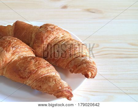 Plate of two fresh butter Croissant pastries served on light color wooden table