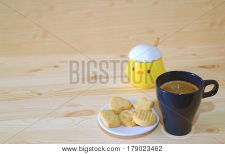 One Cup of Coffee and a Plate of Butter Cookies served on the Wooden Table with Cute Little Chick Sugar Pot