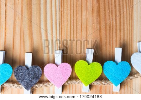Colorful hearts on twine on natural wooden background. Copy space on the top.