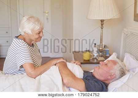 Sick senior man being comforted by his caring and devoted wife while lying in bed at home in the morning