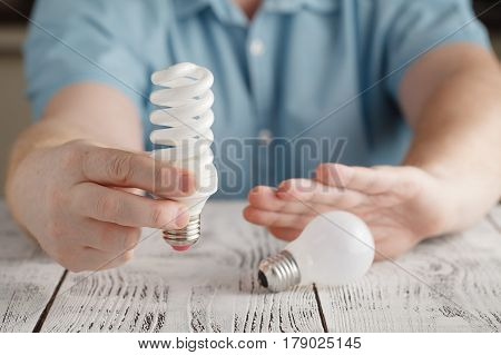Man Hands Decline Glow-lamp And Hold Spiral Lamp Against Wooden Table. Man Hold Lamps In Hands. Ener