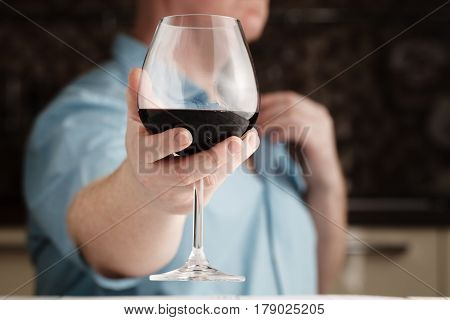 Mid Section Of Man Offering A Glass Of Wine