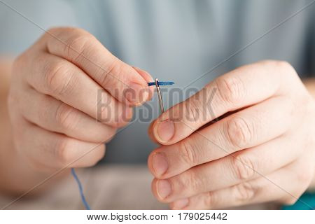 Thread Into The Needle. Close-up Of Man Pulling Thread Into The Needle