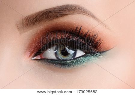 Colorful eye makeup. Cropped close up shot of blue eye of a woman wearing professional multicolored makeup with brown bronze orange and green shades and black eye liner fashion makeup eye shadow macro