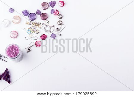 Glass and metal beads amethyst and turmaline stones silver toggle shell rose beads earings metal rings and pliers on white background. Top view.