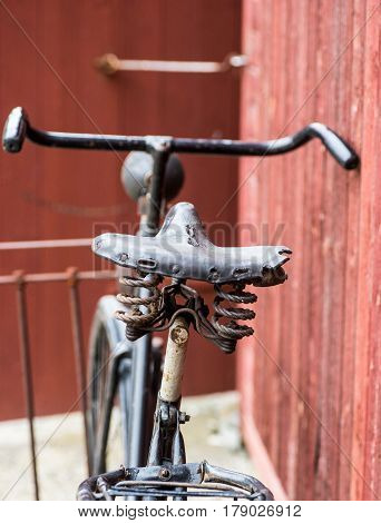 old retro antique black men's bicycle parked up of red wooden fence photographed from behind