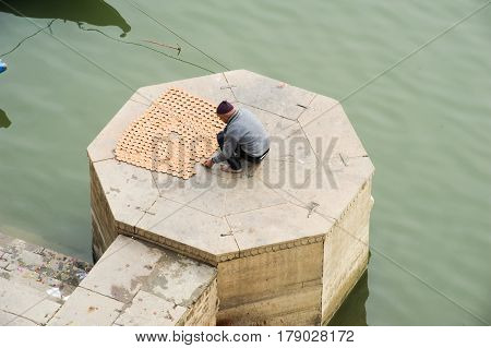 Man Preparing Offers On The Ghats Of River Ganges