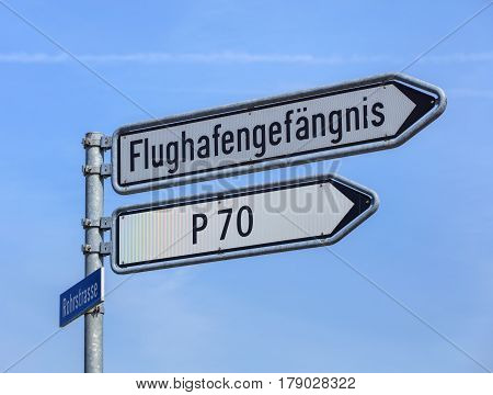 Kloten, Switzerland - 29 March, 2017: sign showing the direction to the Zurich Airport prison (German: Flughafengefangnis). The Zurich Airport Prison is an extradition and remand prison, located in the territory of the Zurich Airport.