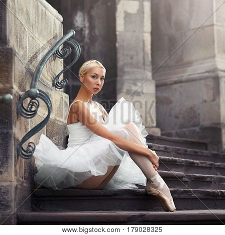 Looking thorough you. Portrait of a young ballerina sitting on an old stairway outdoors with her arms around her knees