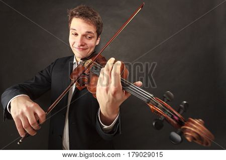 Music passion hobby concept. Man playing violin showing happy emotions and face expressions. Studio shot on dark background