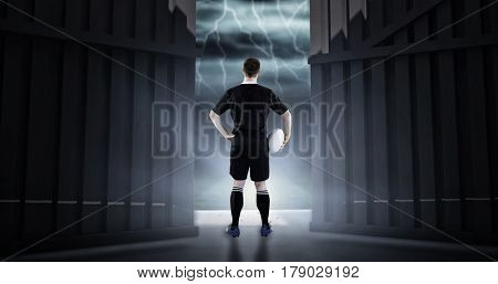 Rugby player holding a rugby ball against football pitch under stormy sky 3d
