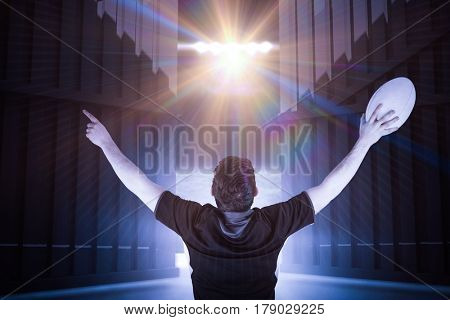 Back turned rugby player gesturing victory against football pitch under bright spotlights 3d