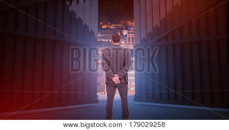 Rear view of classy businessman posing against glowing modern buildings in city 3d