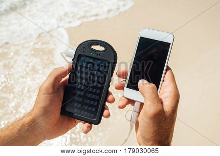 Charger Solar in the hands of men on the background of the sandy beach. Charging smartphone phone from the solar battery.