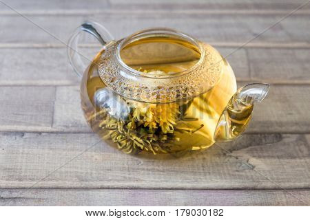 a glass tea pot with Flower Chinese tea on light wooden background