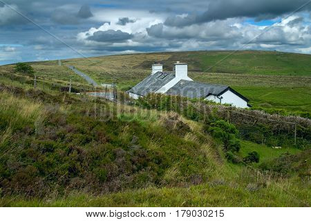 A lone white house stands by the road in the hills of Dartmoor National Park .Devon. England