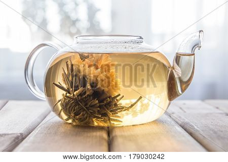 a glass tea pot with Flower Chinese tea on light wooden background in front of the window.