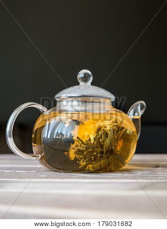 a glass tea pot with Flower Chinese tea on light wooden table in front of dark background. vertical